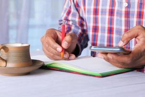 junger Mann, der Smartphone am Schreibtisch schreibt und benutzt foto