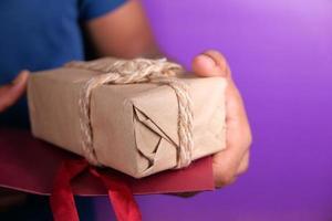 Mann, der ein braunes Geschenk hält foto