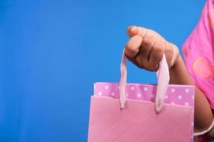 Frau, die rosa Einkaufstasche auf blauem Hintergrund hält foto