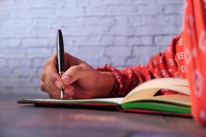 Nahaufnahme der Hand der Frau, die auf Notizblock schreibt foto