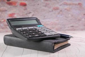 Nahaufnahme von Taschenrechner und Notizblock auf farbigem Hintergrund
