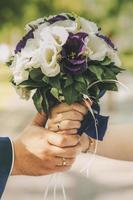 Paar hält einen weißen und lila Blumenstrauß foto
