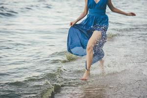 Frau im blauen Kleid im Wasser foto