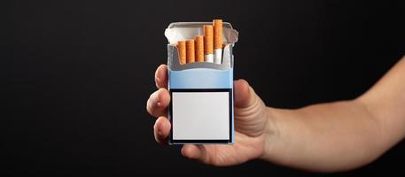 Packung Zigaretten in der Hand auf dunklem Hintergrund mit Kopierraum foto