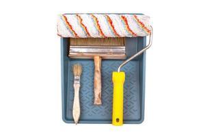 Satz von Werkzeugen zum Malen mit einer Rolle, einem Tablett und einem Pinsel, die auf weißem Hintergrund lokalisiert werden foto