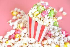 Popcorn, das aus einem Behälter auf rotem Hintergrund verschüttet wird foto