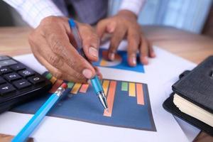 Männerhand mit Stift, der Balkendiagramm auf Papier analysiert