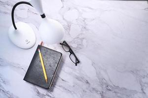 Draufsicht einer Lampe, eines Tagebuchs und eines Bleistifts auf Marmorhintergrund foto