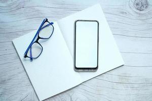 flache Zusammensetzung von Smartphone und Notizblock auf dem Tisch