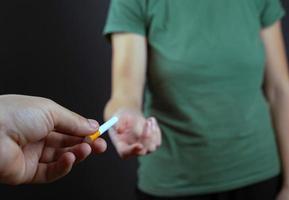 Mann gibt Mädchen eine Zigarette auf einem dunklen Hintergrund foto