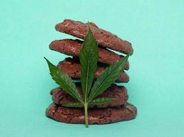 Haferkekse und grünes Cannabisblatt auf einem blauen Hintergrund foto