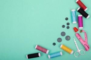 Nähzeugzubehör mit bunten Fäden, Nadeln, Stiften, Schere auf grünem Hintergrund foto