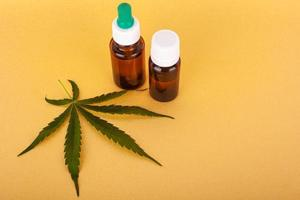 medizinischer Cannabisextrakt, der thc und cbd auf gelbem Hintergrund enthält foto