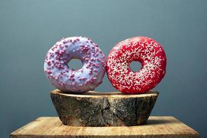 zwei runde glasierte Donuts, bestreut mit süßem Zuckergussrot und Purpur auf einem Holzsockel auf grauem Hintergrund foto