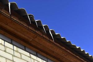 Eiszapfen auf dem Dach des Hauses im Winter foto