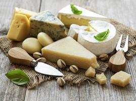 verschiedene Käsesorten mit Basilikum und Nüssen foto