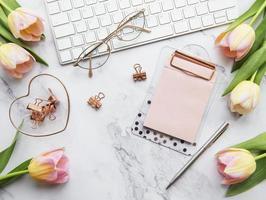 Freiberufler- oder Blogger-Arbeitsplatz mit Tastatur, Notizblock und Tulpen foto