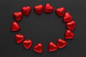 rote Schokoladenherzen angeordnet auf schwarzem Hintergrund foto