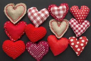 gemusterte Herzen des Valentinstags angeordnet auf schwarzem Hintergrund foto