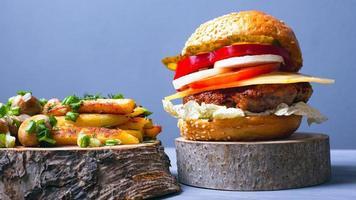 leckerer Hamburger mit Fleischkotelett, Gemüse und Käse mit weichem Brötchen, Pommes und Champignonpilzen foto