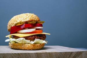 großer saftiger Burger mit Kopienraum auf grauem Hintergrund foto