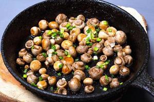 Gebratene Champignons mit Frühlingszwiebeln in einer gusseisernen Pfanne auf einem Holzständer foto