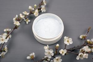 weißes rundes Körperpeeling mit Zweigen der weißen Blumen auf einem grauen Hintergrund foto