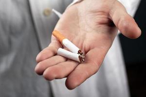 zerbrochene Zigarette in der Hand einer Nahaufnahme eines Arztes foto