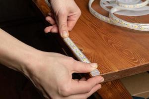 Der Meister klebt den LED-Streifen aus dem Schrank in die Nische des Regals foto