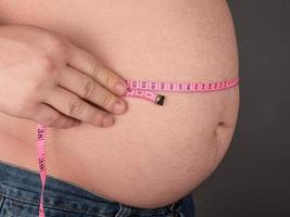 dicker Bauch und Zentimeter, fettleibiger Mann foto