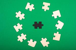 Teile des Puzzles färben weiß und schwarz, auf einem grünen Hintergrund foto
