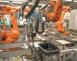 Der automatische Roboterarm in der Fabrik ersetzt die menschliche Arbeit. Automatisierung der Produktion zum Zeitpunkt des Personalmangels foto