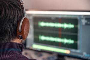Mann im Studio nimmt Gesang, Stimme und Musik für den kommerziellen Gebrauch auf und modifiziert sie foto