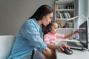 Mutter hilft Kind mit virtueller Schule foto