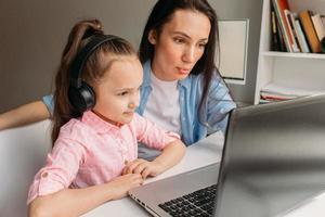 Mutter und Tochter benutzen einen Laptop für die virtuelle Schule foto