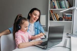 Mutter hilft Tochter mit der Schule zu Hause foto