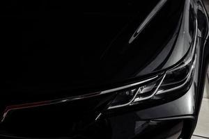 Scheinwerfer des modernen prestigeträchtigen schwarzen Autos hautnah foto