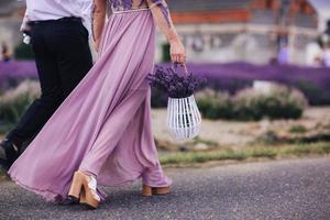 schöne junge Frau in einem blauen Kleid hält einen Blumenstrauß Lavendel in einem Korb beim Gehen im Freien durch ein Weizenfeld bei Sonnenuntergang im Sommer. Provence, Frankreich. getöntes Bild mit Kopierplatz foto