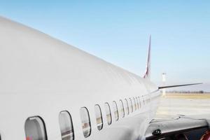 Flugzeug Bullauge Seitenfenster Flugzeug. weißes schweres Passagierflugzeugtriebwerksflugzeug auf der Landebahn am Flughafen gegen blauen Himmel, Luftfahrttransportthemahintergrund foto