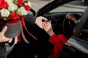 höflicher Mann mit einem Blumenstrauß, der einer Geschäftsfrau in einem roten Anzug hilft, aus einem Parkplatz im Freien herauszukommen foto