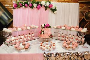 rosa Hochzeitstorten des Schokoriegels, die durch Blumen verziert werden, die an einem festlichen Tisch mit Wüsten, Erdbeertörtchen und Cupcakes stehen. Hochzeitskonzept foto