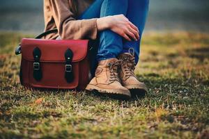 stilvolles junges Mädchen in braunen Schuhen und einem warmen Mantel, der im Park mit einer roten Tasche sitzt. foto