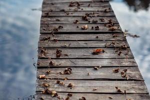 Eine Holzbrücke ist mit Herbstlaub bedeckt. Herbstahornblätter auf Holztisch. fallender natürlicher Hintergrund der Blätter foto