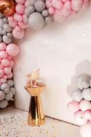 köstlicher Hochzeitsempfang. Geburtstagstorte auf einem Hintergrundballonpartydekor. Speicherplatz kopieren. Feierkonzept. trendiger Kuchen. Schokoriegel. Tisch mit Süßigkeiten, Dessert. foto