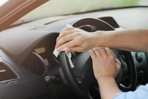 Fahrer, der Feuchttücher zur Desinfektion eines Autolenkrads gegen Viren oder Coronaviren verwendet. Auto Reinigung. selektiver Fokus. foto