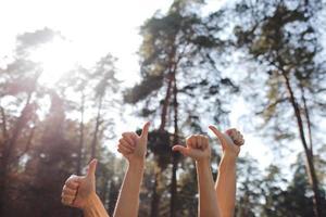 menschliche Hände, die Daumen oben lokalisiert auf einem natürlichen Hintergrund zeigen. männliche und weibliche Hände, die ok Zeichen im Park zeigen. selektiver Fokus. Speicherplatz kopieren. foto
