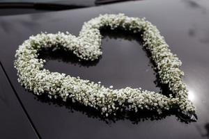 Hochzeitsauto verziert mit einem Herzen der weißen Blumen foto