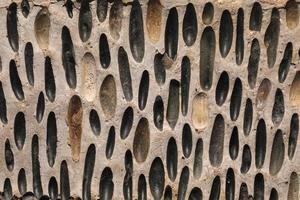 Die Oberfläche des Bürgersteigs ist wunderschön mit bunten Kieselsteinen gepflastert. bunter Steinhintergrund. Gehweg von Kieselsteinen. selektiver Fokus foto