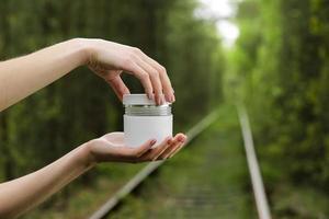 junge weibliche Hände öffnen ein weißes Glas Creme für Gesicht oder Körper. Bio natürliche Hautpflegeprodukte auf einem grünen natürlichen Hintergrund. Verpackung von Lotion oder Creme. Schönheitskosmetik-Hautpflegekonzept foto