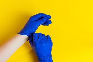 Frau zieht blaue Handschuhe aus foto